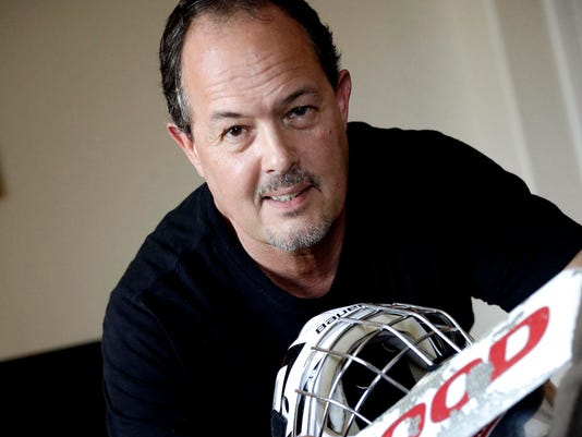 In this Thursday, July 28, 2016, photo, Tim Richmeier poses for a photo with some of his 15-year-old son's hockey equipment, in Phoenix. Richmeier was spending about $5,000 a season using his tax refunds, halting contributions to his 401(k), and putting travel expenses on a credit card, including $6,000 he's still paying off, so his son could play on a travel hockey team. (AP Photo/Matt York)