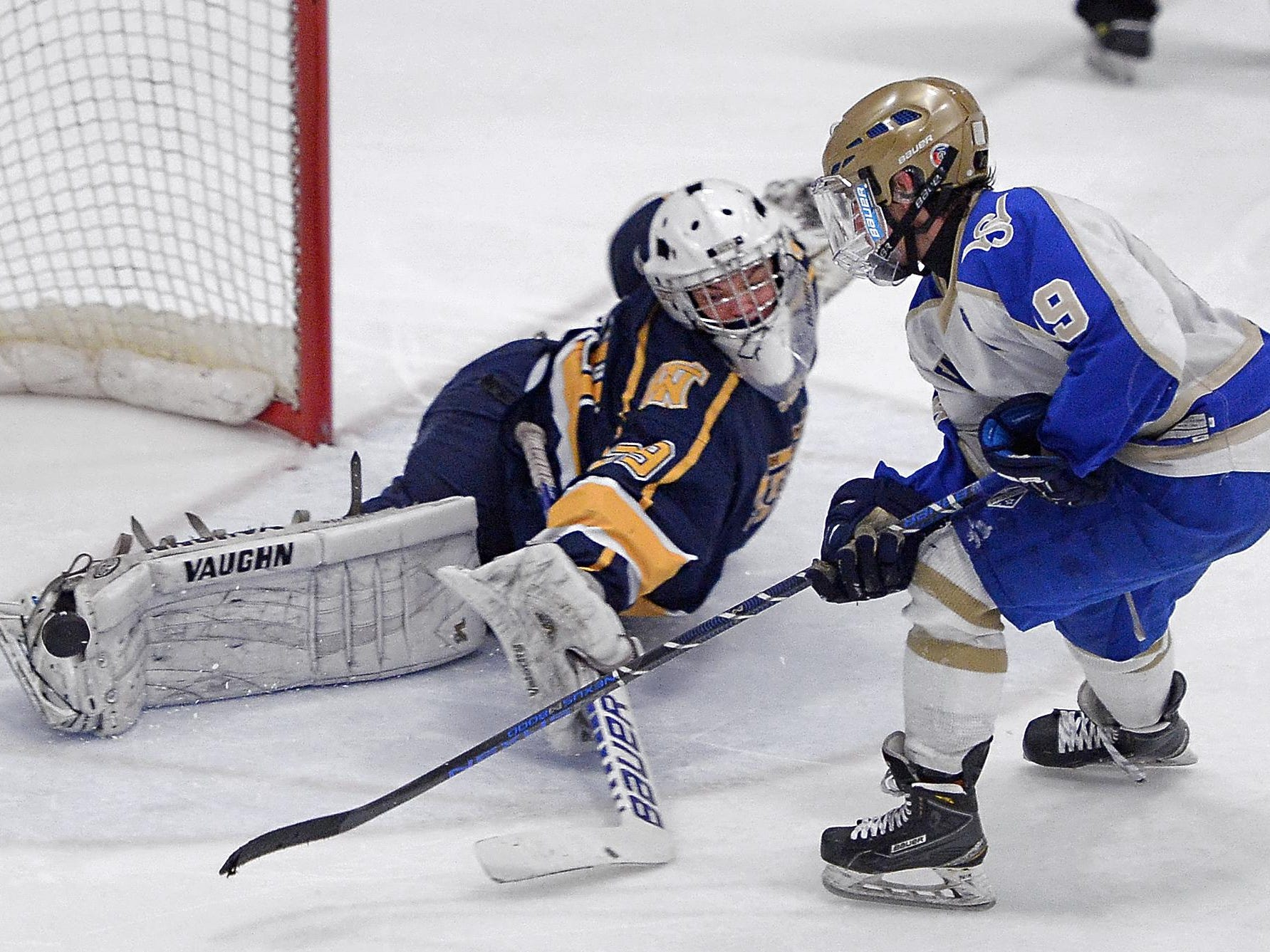 Webster Thomas goalie Dalton Jerzak, left, stops a penalty shot by Webster Schroeder's Matt Montgomery in the third period to preserve the 2-2 tie Webster Ice Arean as part of the Robert J. Smith Memorial High School Hockey Showcase on Saturday.
