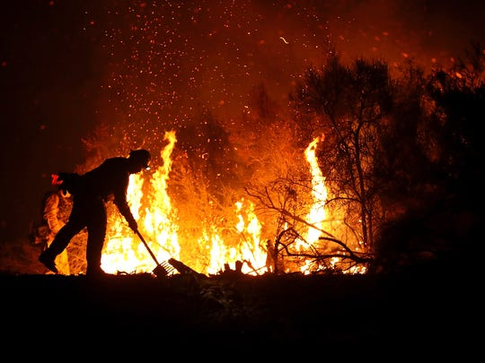 A Cal Fire firefighter monitors a back fire while battling