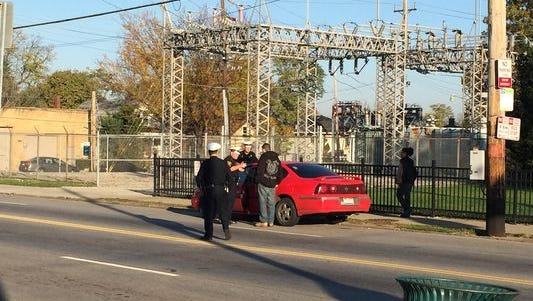 Police speak to the suspect at the scene in East Price Hill on Friday. Police say he struck a 74-year-old man with his vehicle.