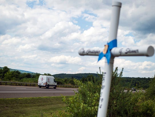 Cars pass a roadside cross in memory of murdered New