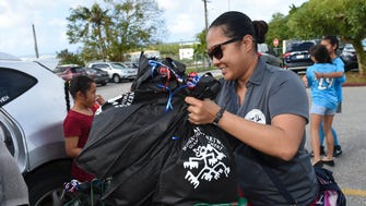 Officer Harri Lee Matsumoto-Webber, the president of the Guam Police Department's Women's Advisory Network, transports bags of containing feminine care products for Alee Shelter resident survivors at Catholic Social Service in Barrigada on Dec. 22, 2017.