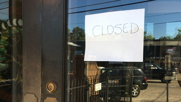 "A ""closed"" sign hangs on the door of Sinclair's in"