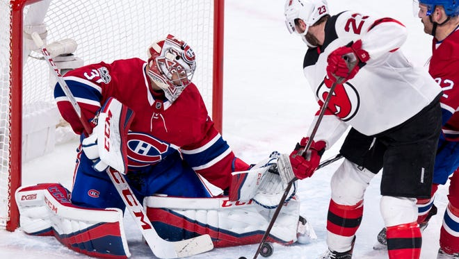 Montreal Canadiens goaltender Carey Price stops New Jersey Devils' Stefan Noesen during the second period of an NHL hockey game, Thursday, Dec. 14, 2017 in Montreal.