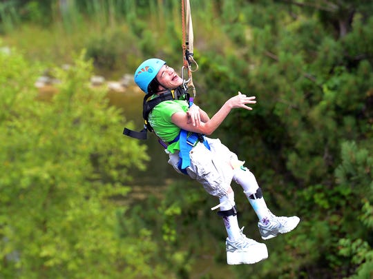 The NEW Zoo Adventure Park zip line hosted a group of physically handicapped adventurists Aug. 11, 2014.  Linn Allen smiles as she rides the zip line wire from the top of the 50-foot zip line tower.