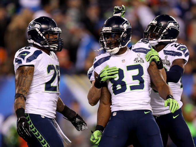 EAST RUTHERFORD, NJ - FEBRUARY 02:  Wide receiver Doug Baldwin #89 of the Seattle Seahawks celebrates his 10-yard touchdown with Michael Robinson #26 and Jeremy Lane #20 in the fourth quarter against the Denver Broncos during Super Bowl XLVIII at MetLife Stadium on February 2, 2014 in East Rutherford, New Jersey.  (Photo by Jeff Gross/Getty Images)