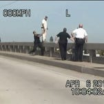While two deputies distracted him, another was able to pull him off the railing.