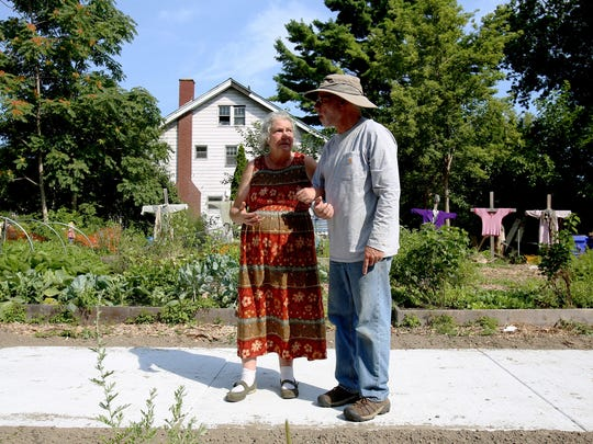 From left, Nicola Binns walks in front of her Detroit garden with Drew Lathin of Creating Sustainable Landscapes while talking about the rain garden being installed at her home on Wednesday, August 9, 2017.