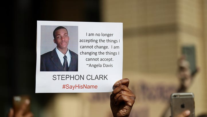 A protester holds a photo of Stephon Clark during a