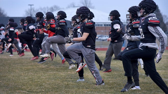 Milan's football players loosen up for practice Monday. The Big Reds will play Williamston Saturday in the Regional Final at Lansing Catholic at 5:30pm.