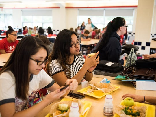 Hanover High School freshman Jackie Gonzalez, middle, eats an apple for lunch with classmate Bethany Romero, left, during lunch in September.