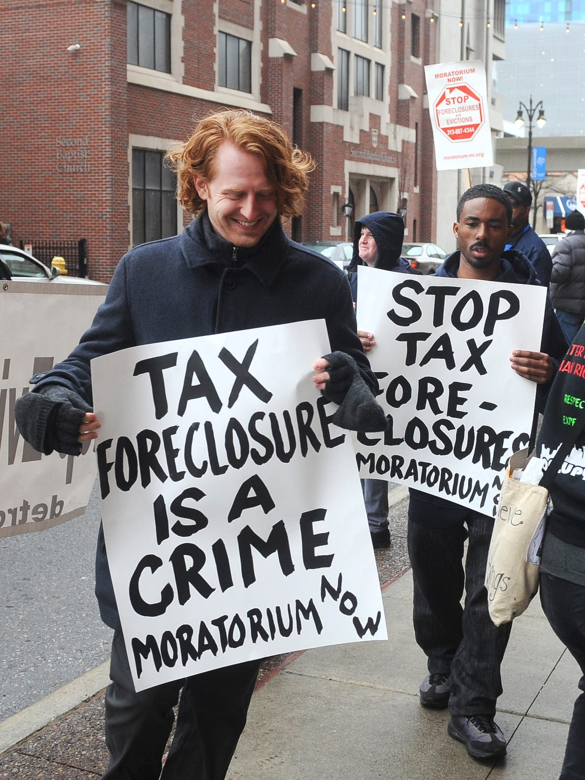 Protestors march outside the Wayne County Treasurer's