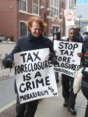 Protestors march outside the Wayne County Treasurer's office in March. The county has stopped a long practice of avoiding foreclosures on homes with delinquencies of less than $1,700.