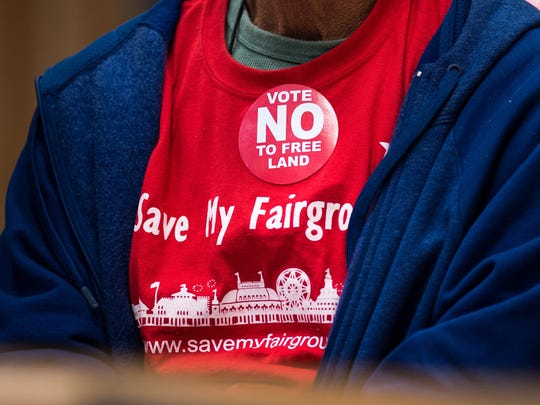 "Opponents wear ""vote no"" stickers before a vote on"