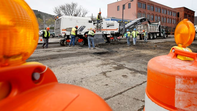 Area municipal department of public work crews repair Denison Parkway between Pine and Cedar streets Thursday to level out the surface following a February water main break that bubbled the pavement.