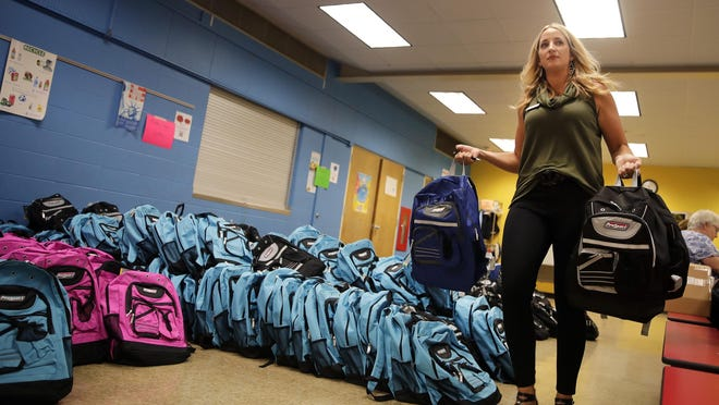 Leslie Wilson, with the Neenah-Menasha Emergency Society, carries backpacks that were distributed to students during a past Back to School Fair at Horace Mann Middle School in Neenah.