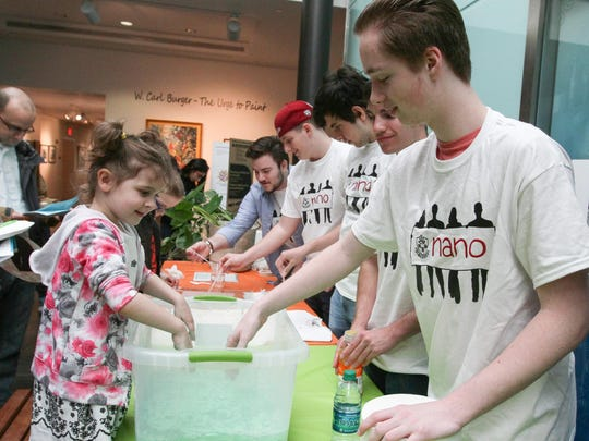 Morristown Nano Scales Science Engineer students help children try out dry sand during Astronomy Day.