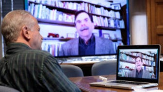 On the big screen, Cornucopia Institute co-founder Mark Kastel is interviewed by Milwaukee Journal Sentinel reporter Rick Barrett via Skype.