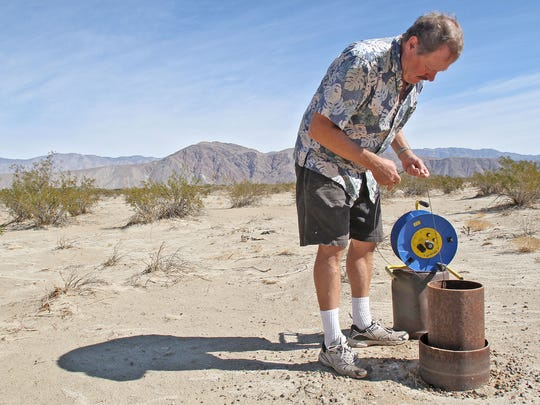 John Peterson takes a water level measurement at an old well site in Borrego Springs.