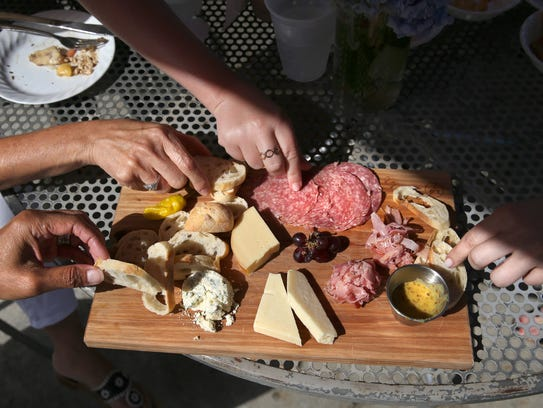 The group enjoys the Finger Lakes Meat and Cheese Board