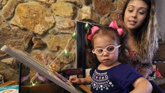 Eleanna Rivas, 3, finds puzzle pieces that she can identify by shape and color with her mother, Anna Rivas, in their Milwaukee home. Eleanna's optic nerves never fully developed that has resulted in limited vision and her eye's focal point is off center.