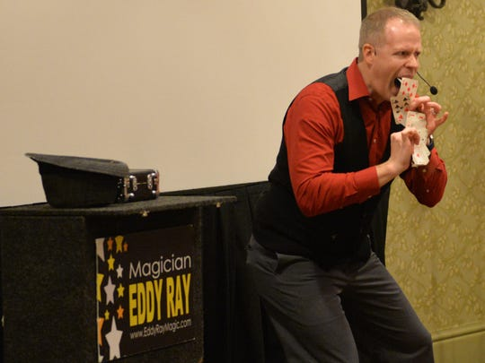 Magician Eddy Ray performs a card trick during a show held at the Hershey Lodge on Friday, December 30, 2016.
