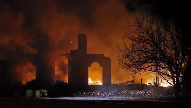 In this photo taken on Monday, Dec. 22, 2014, a smoldering fire is all that remains of a home belonging to Dallas Cowboys NFL football player Rolando McClain in Tuscaloosa.