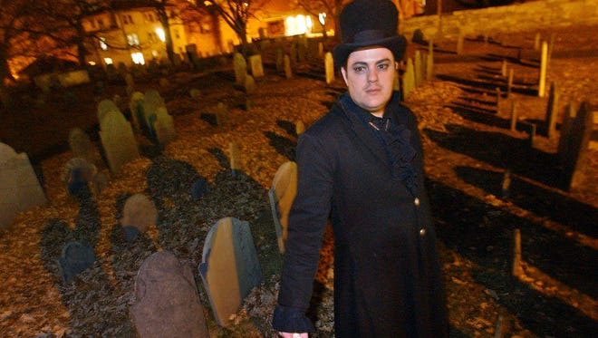 In this Dec. 22, 2003 file photo, Christian Day poses in the Old Burying Ground in Salem, Mass. A judge is scheduled to hear a suit on Wednesday, Oct. 28, 2015, in Salem District Court brought by Lori Sforza, who calls herself a witch priestess, accusing Day, a self-proclaimed warlock, of harassing her online and over the phone for three years.