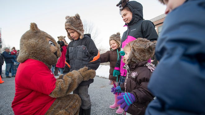 Dover Doug hugs a group of children with groundhog hats after making his prediction for more winter February 2, 2016 in Dover.