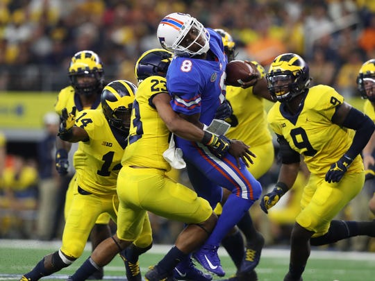 The Michigan defense crunches Florida Gators quarterback