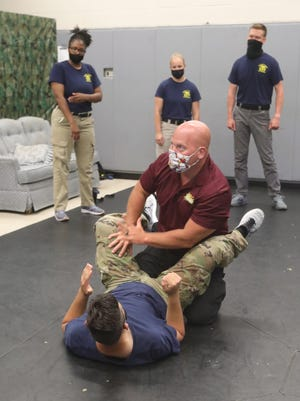 Instructor Jeff Begue demonstrates defensive tactics with Nathan May during a training class at the Summit County Sheriff's Office Training Bureau on Monday, June 22, 2020, in Green, Ohio.