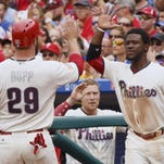 Phillies catcher Cameron Rupp, left, celebrates after scoring on a hit by Tommy Joseph with Odubel Herrera, right, during Monday's win over the Braves.