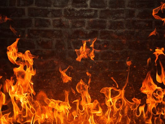 Fire flames and dark brick texture on background