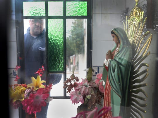 Jorge Garcia looks into a shrine of the Virgin of Guadalupe built by a neighbor. He was deported recently from Detroit and is now trying to adjust to life in a small town outside of Mexico City.