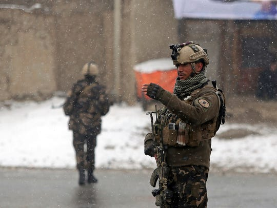 Afghan security personnel stand guard at the site of