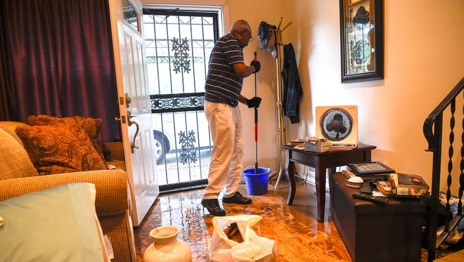 Calvin Lake cleans the floor of his flooded home on West Hamilton Avenue on Friday, Sept. 1, 2017 in Nashville. Lake has lived in his Bordeaux home since 1968.