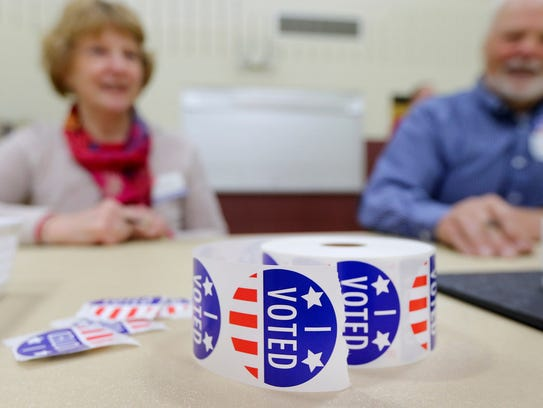 "A roll of ""I Voted"" stickers sit on a table in front"
