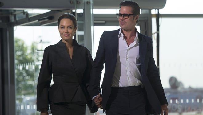 Angelina Jolie and Brad Pitt pose for pictures upon arrival on the fourth day of the Global Summit to End Sexual Violence in Conflict in London on June 13, 2014.