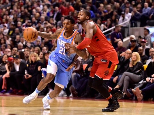 CORRECTS RAPTORS PLAYER TO CJ MILES Los Angeles Clippers guard Lou Williams (23) drives on Toronto Raptors CJ Miles (24) during second half NBA basketball action in Toronto on Sunday, March 25, 2018. (Frank Gunn/The Canadian Press via AP)