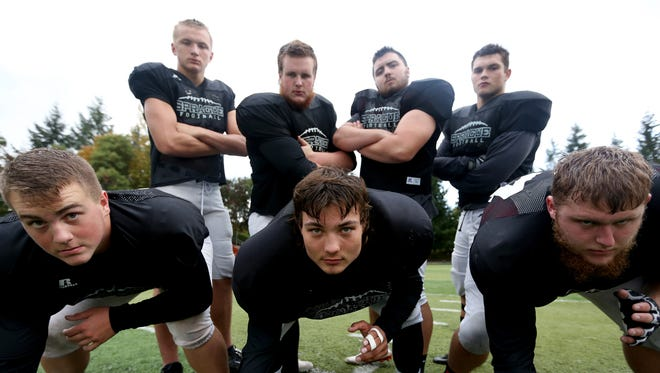 The Sprague football offensive line (front row, l-r) Tanner Sorensen, Spencer Nofzinger, Kyle Rosenau, (back row, l-r) Teagan Quitoriano, Bryce Perkins, Ryan Pe–a and Tristan Friederick, pose for a photo at Sprague High School on Wednesday, Oct. 5, 2016.