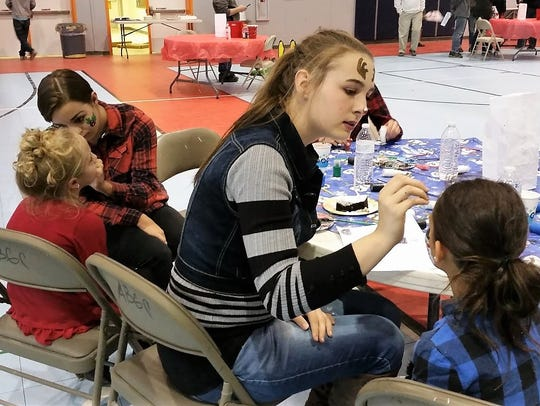 Members of the Aztec Key Club work the face painting