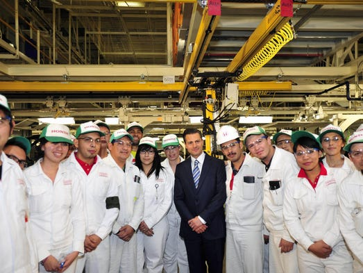 Handout photo released by the Mexican Presidency press office showing Mexican President Enrique Pena Nieto  while posing with workers after the opening of the new Honda car factory in Celaya, Guanajuato state, Mexico