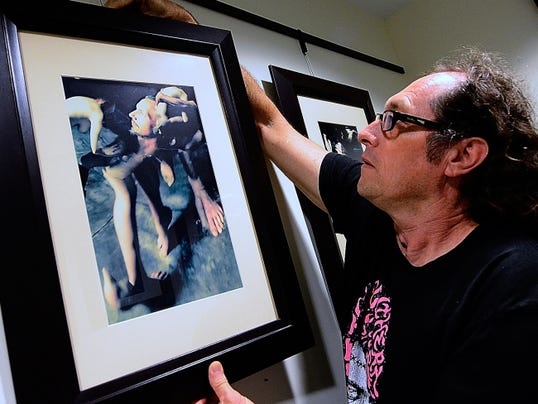Freddie Graves hangs his photographs Wednesday at Marketview Arts for the upcoming exhibition Abstraction of Form.
