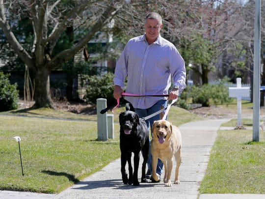Scott Brandle, owner of River Run Pet Sitters/Ocean Walk Pet Sitters, a Shrewsbury/Brick based business which provides a long range of pet care services, walks his dogs, Cooper and Ripley, near his home in Brick.