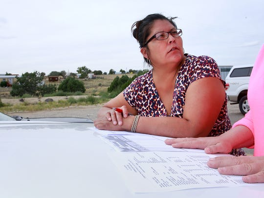 Vera Pierce, a resident of the Morning Star subdivision, discusses her water bill with Kalee Grothe, general manager of Dino's Mart, on Sept. 7 at 405 County Road 390 in Crouch Mesa.