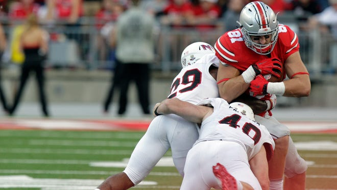 Ohio State tight end Nick Vannett, right, is tackled by Northern Illinois defenders Paris Logan, left, and Sean Folliard during the fourth quarter of an NCAA college football game Saturday, Sept. 19, 2015, in Columbus, Ohio. Ohio State won 20-13.