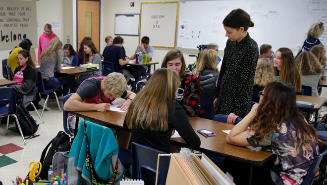 Kaley Olles (right) works with students in her English class at Oconomowoc High School.