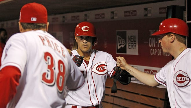 Cincinnati Reds shortstop Kris Negron (17) is fist bumped by Cincinnati Reds manager Bryan Price (38) and the batboy in the dugout following his sacrifice bunt.