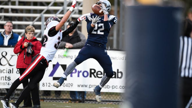 Reitz's Isaiah Dunham beats pressure from East Central's Zachary Theobald to pull in a touchdown pass as the Evansville Reitz Panthers play the East Central Trojans in the 4A regional at the Reitz Bowl Saturday, November 12, 2016.