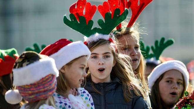 Kids sing Christmas carols to people lined up along Coastal Highway in Ocean City for a previous Ocean City Christmas Parade. This year's parade will be held on Saturday.